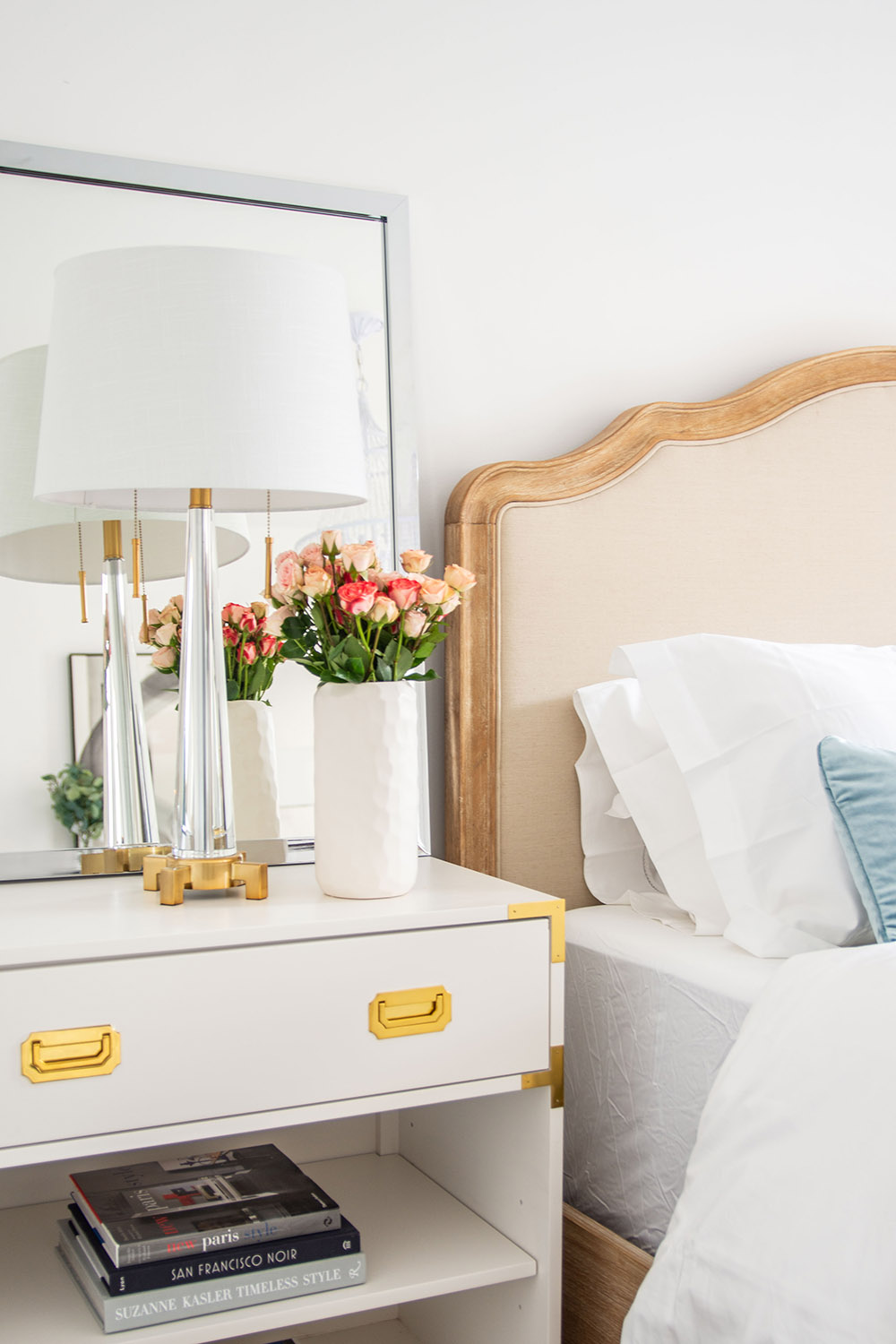 A bedroom scene featuring a nightstand with a lamp and flowers.
