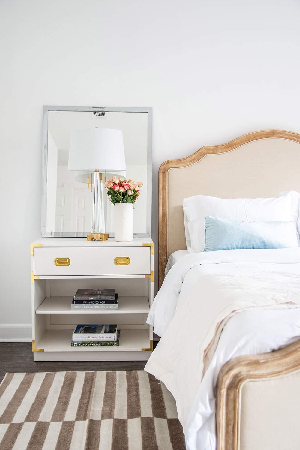 A bedroom scene featuring a bed and nightstand with a lamp and flowers.