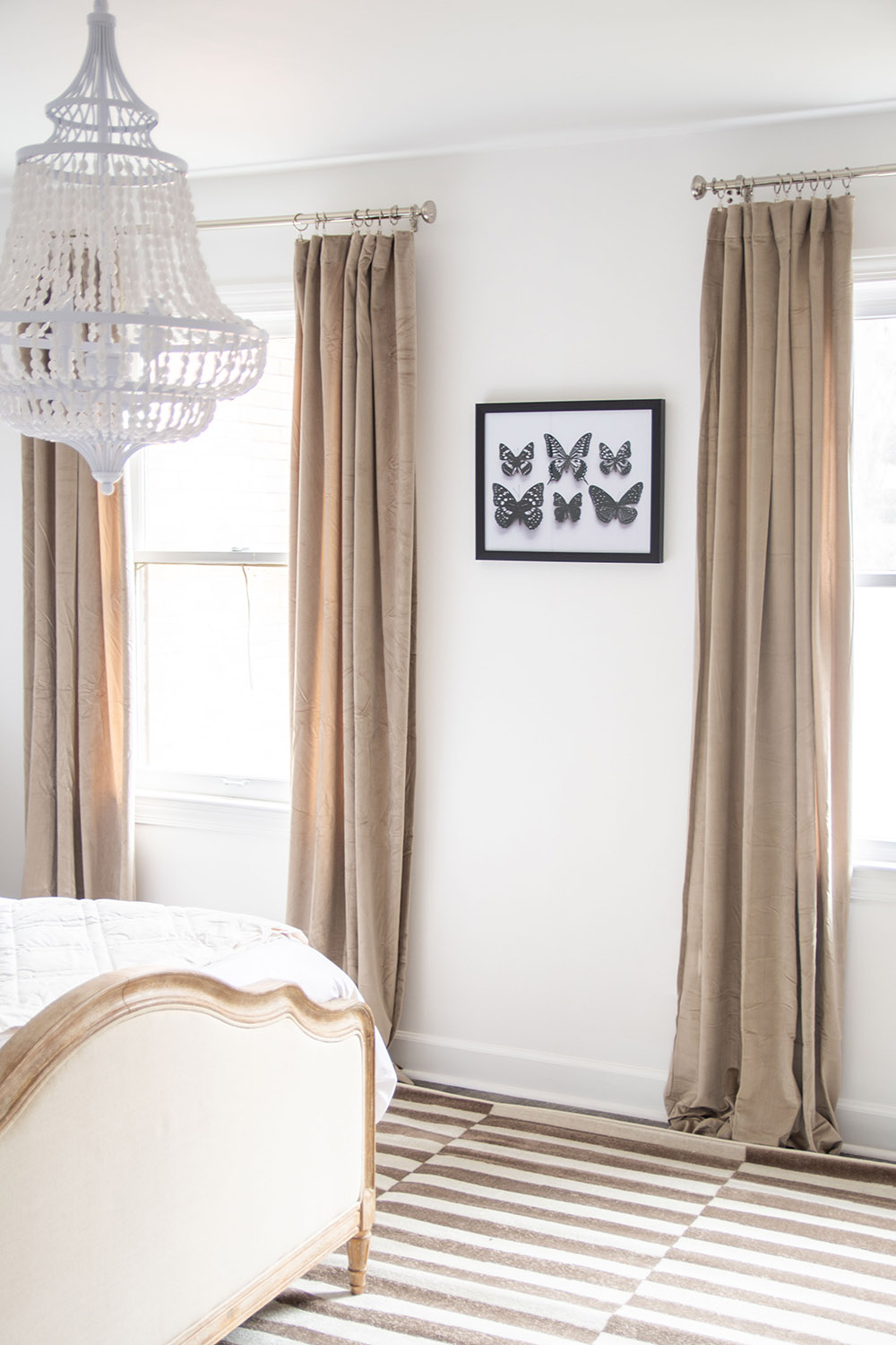 A bedroom scene featuring a modern light fixture overhead, neutral colored curtains and wall art.