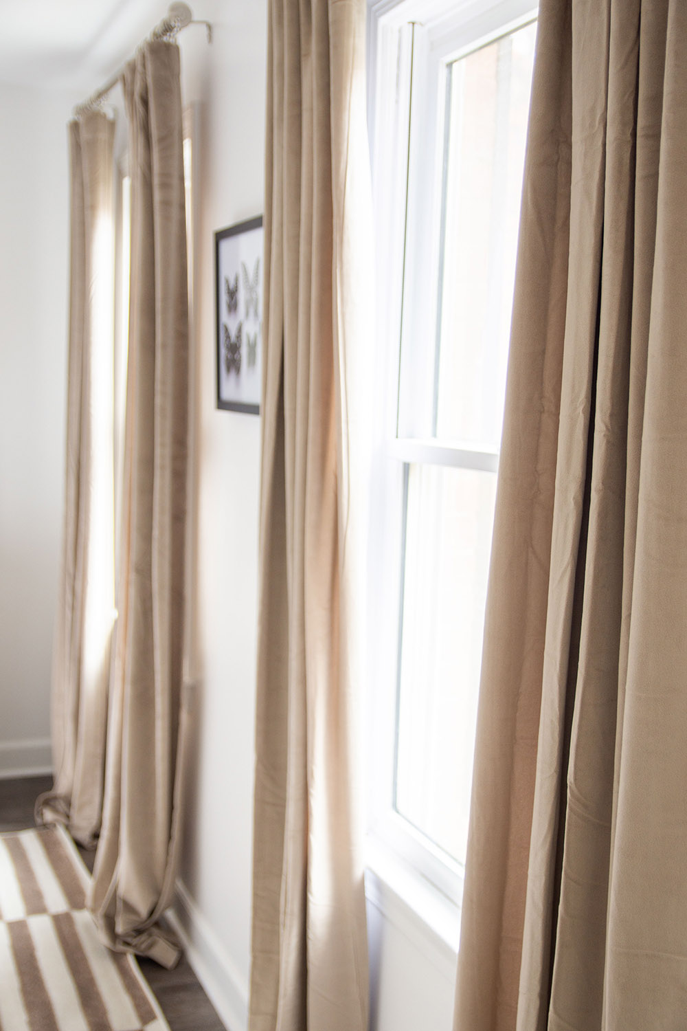 A white wall with neutral colored curtains and art.