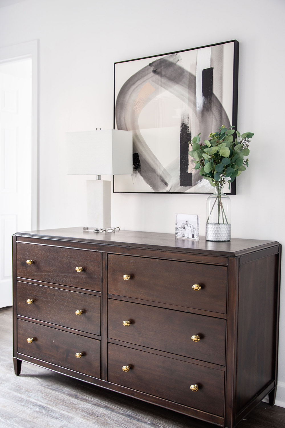 A bedroom wall featuring a wooden dresser and other decor items.