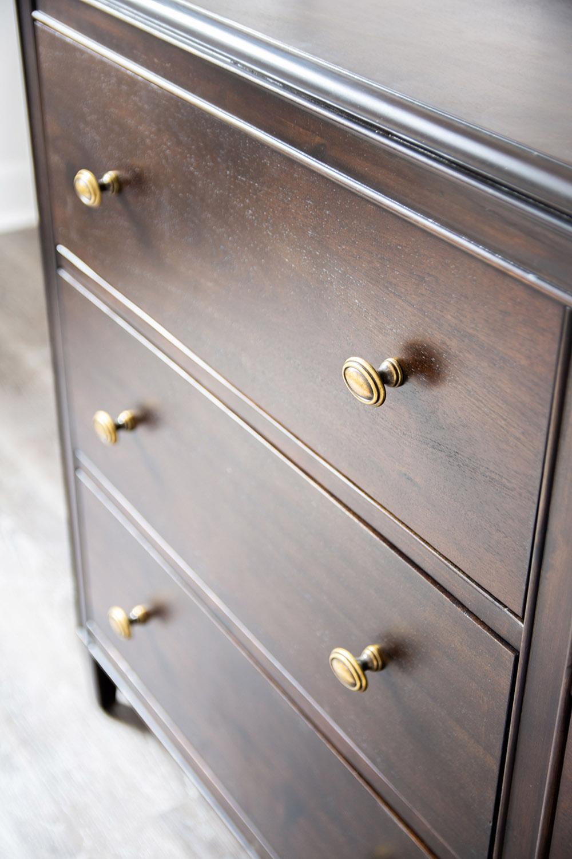 Wooden dresser with gold handles.