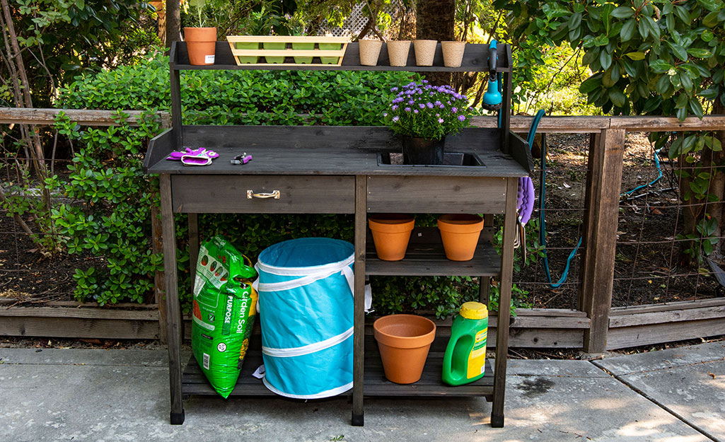 Potting bench with terra cotta pots and potting soil