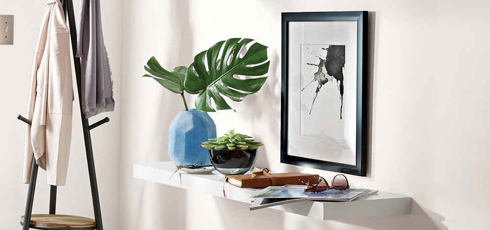 A white floating shelf with a vase and several small personal items on it.