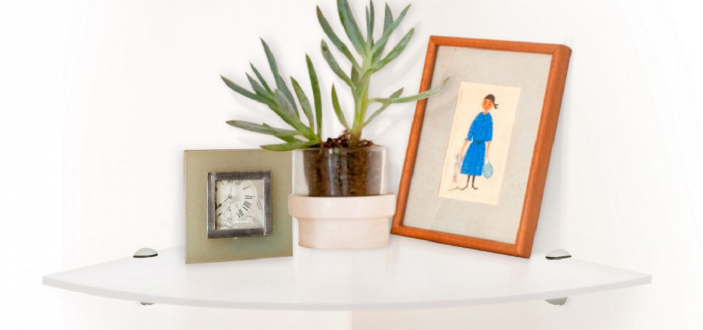 A brown wood corner shelf containing a small statue and a photo frame.
