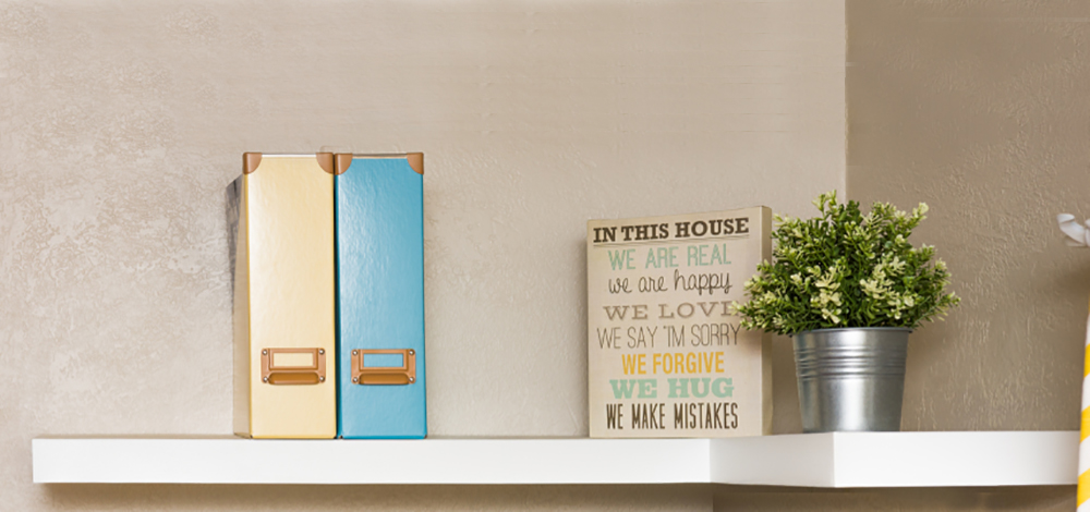 An L-shaped floating shelf holding two magazine storage boxes and small decor items.