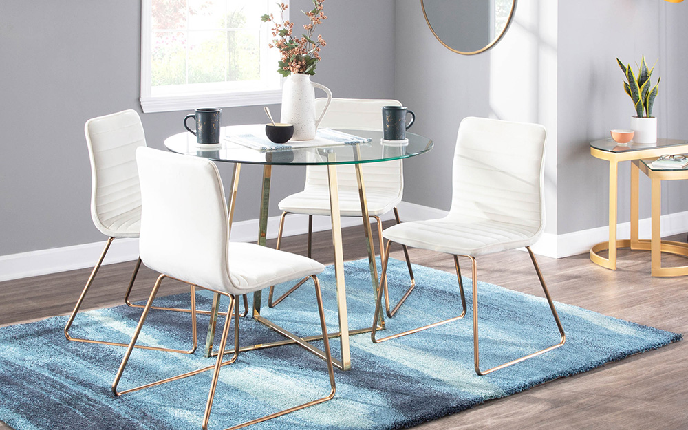 A round glass dining table on a blue area rug.