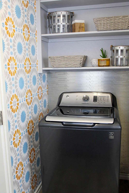 A gray top load washing machine sits below a wall of open shelving.