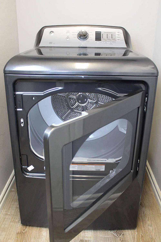 A new gray GE dryer with the door open.
