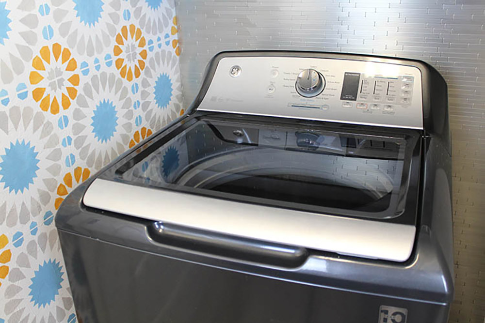 The top of a new gray GE top load washing machine.