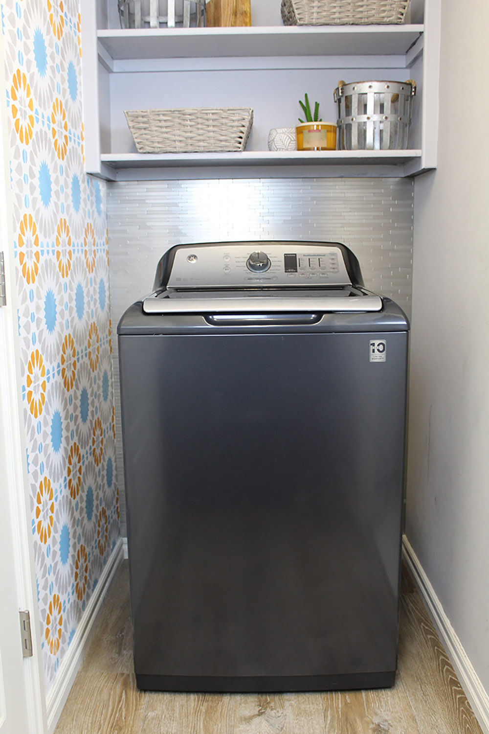 A gray GE washing machine in front of a wall of metal backsplash.