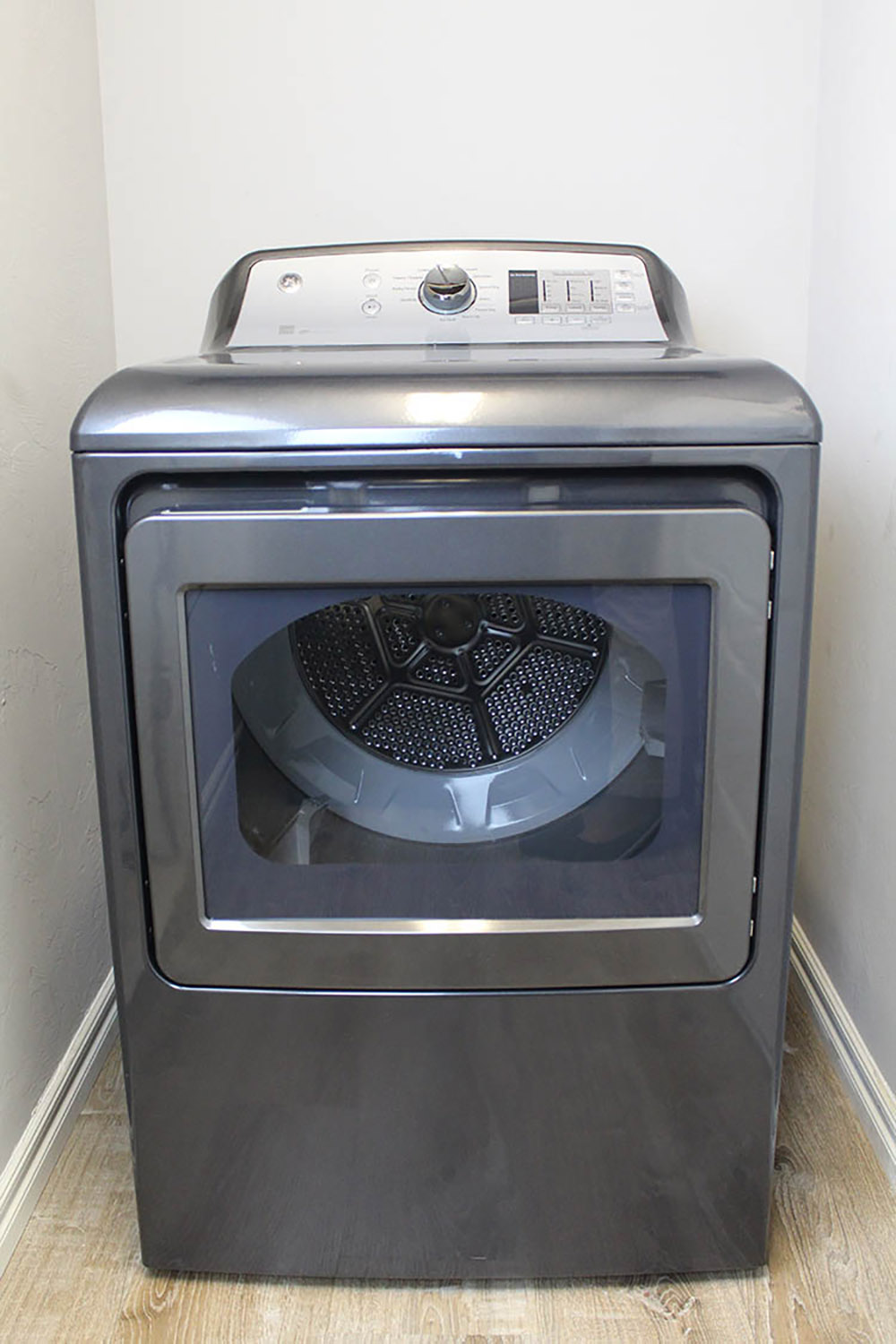 A gray GE dryer sits in an empty laundry room with blank walls.