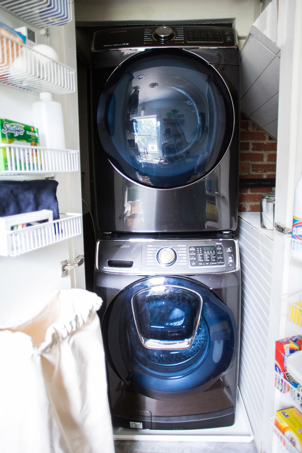 A closet with a washing machine, a dryer, and shelves on the doors.