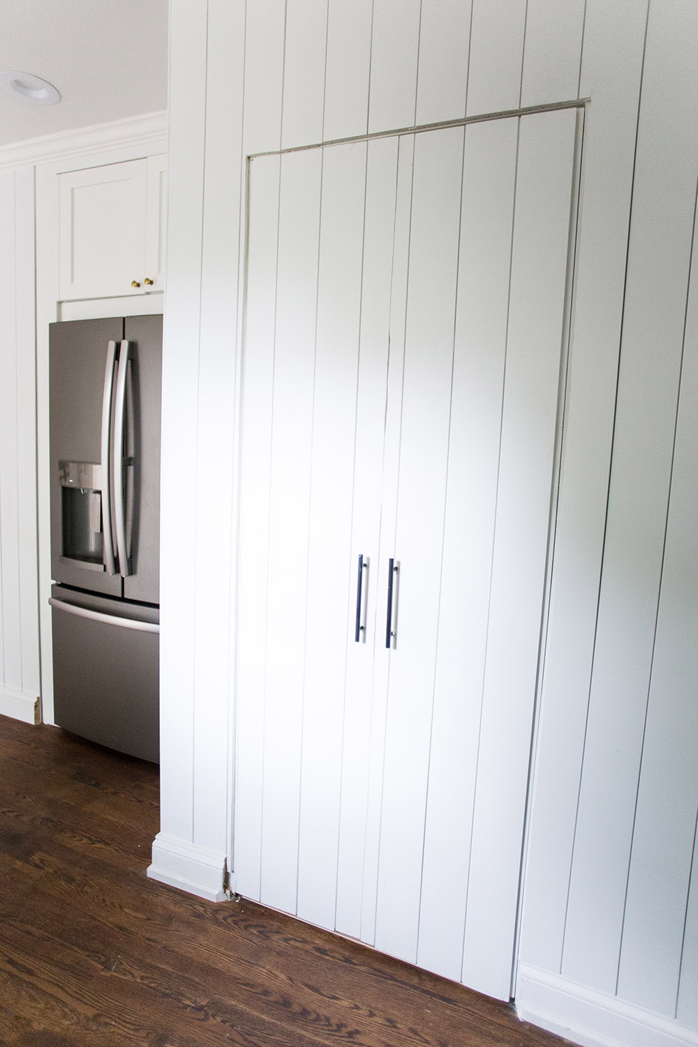 A white plank wall with double doors and silver handles.