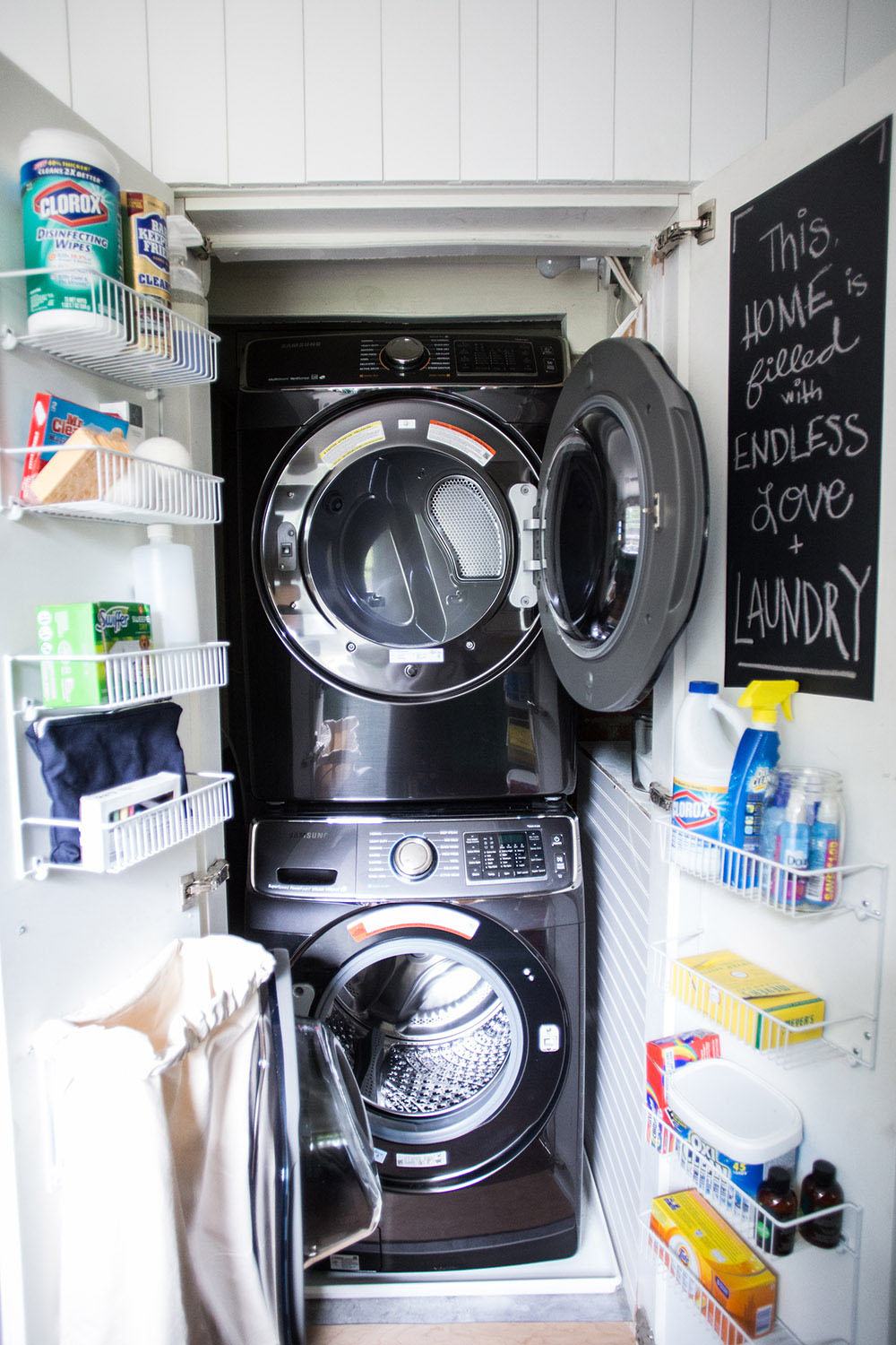 A closet with a open washing machine, a dryer, and shelves on the doors.