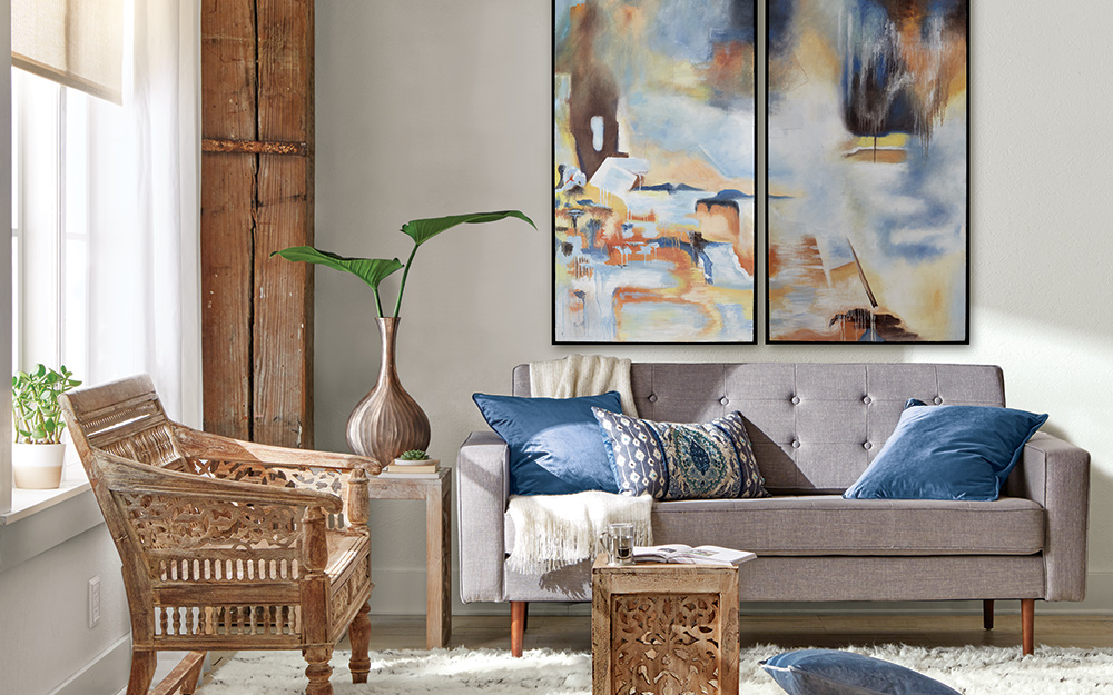 A large painting hangs from the wall of a small living room with a matching carved chair and end table.
