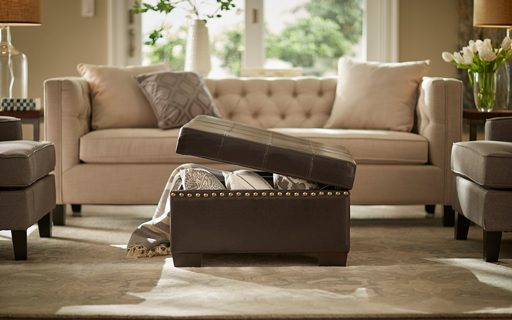 A brown ottoman provides hidden storage in a living room with earth-toned furnishings.