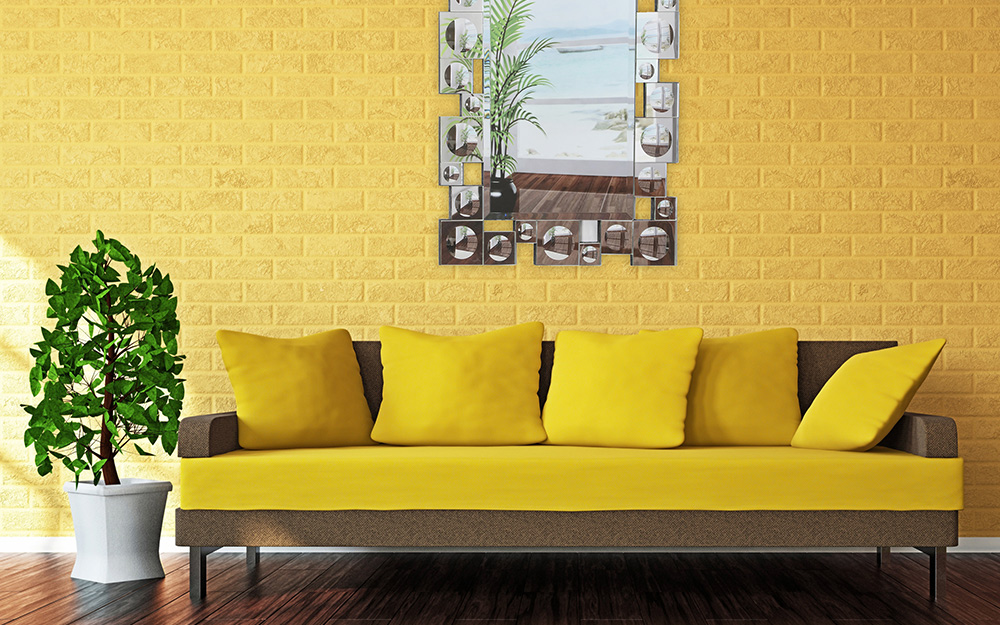 A yellow sofa with matching throw pillows stands against a yellow wall in a small living room.