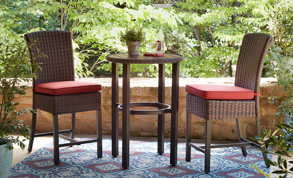 A bar-height table and chairs on a small patio.