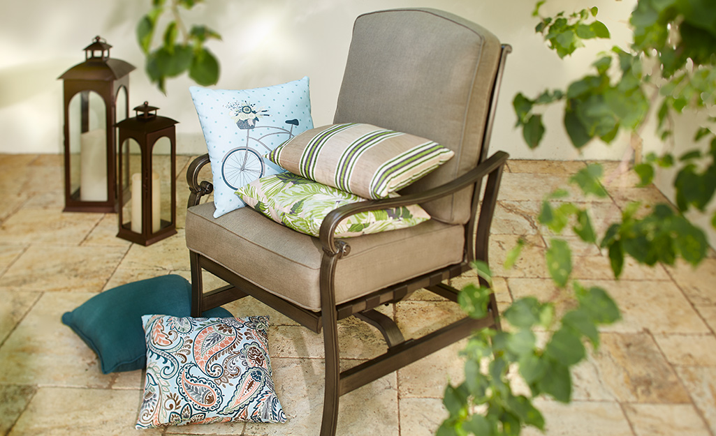 Throw pillows and outdoor patio accessories placed around a chair.