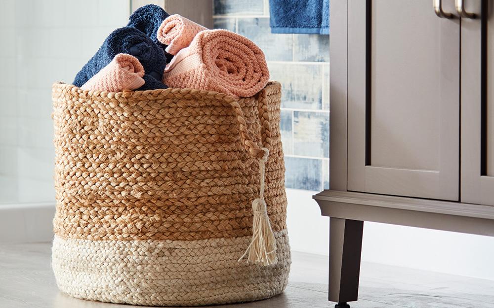 Một chiếc giỏ làm bằng vật liệu tự nhiên đựng khăn tắm.