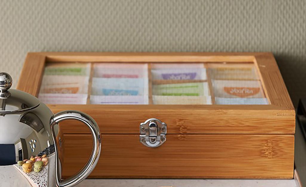 Hộp trà có nắp nhìn xuyên thấu chứa các loại gia vị và đặt trên mặt bàn.