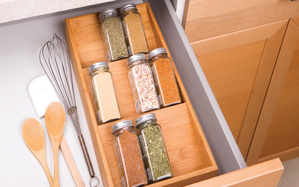 Một ngăn kéo mở với một số đồ dùng nhà bếp và một ngăn đựng gia vị có thể tháo rời, kéo ra để đựng những chai gia vị thủy tinh.