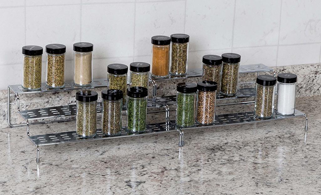 Một giá gia vị nhiều tầng trên mặt bàn chứa các lọ gia vị thủy tinh.