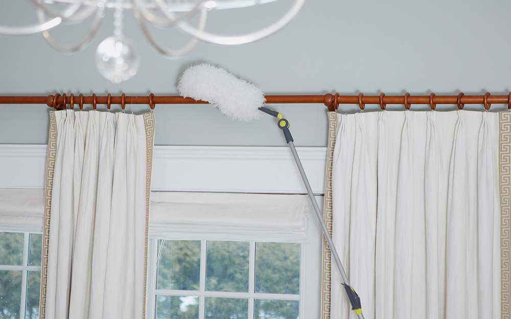 A long-handled duster being used to clean a curtain rod