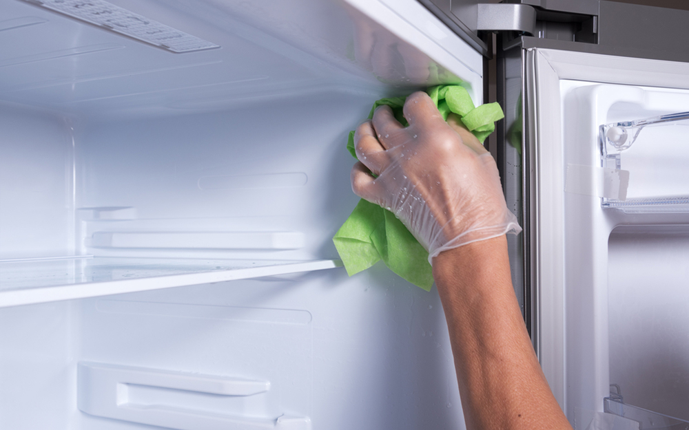 A person using a cloth to wipe the interior of a refrigerator