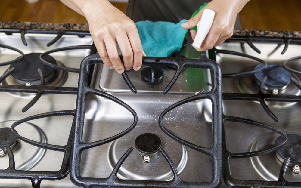 A person using a spray bottle and pad to clean a stovetop