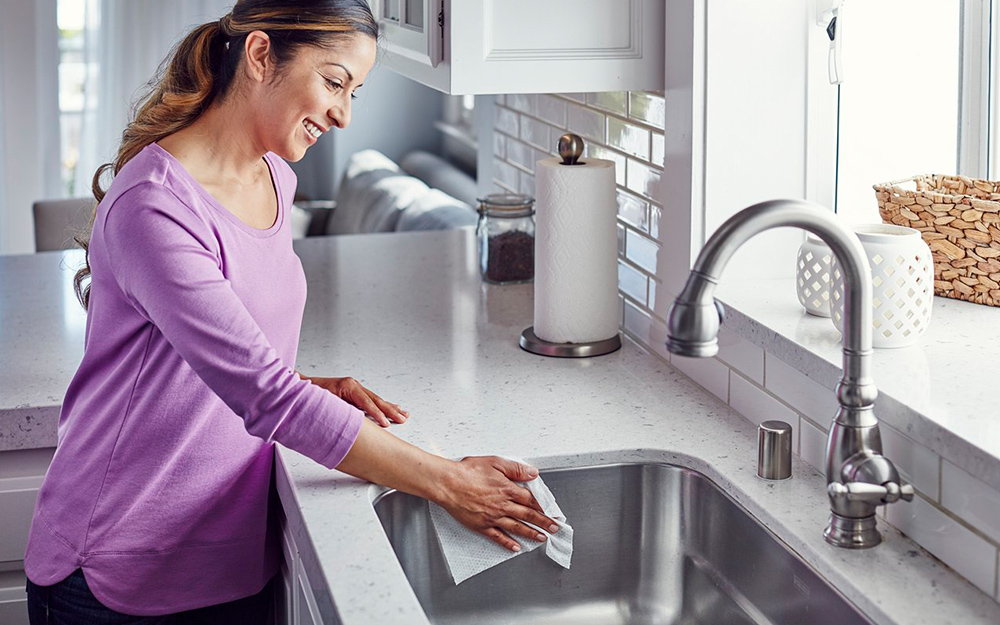 Woman cleaning a kitchen sink with a cloth