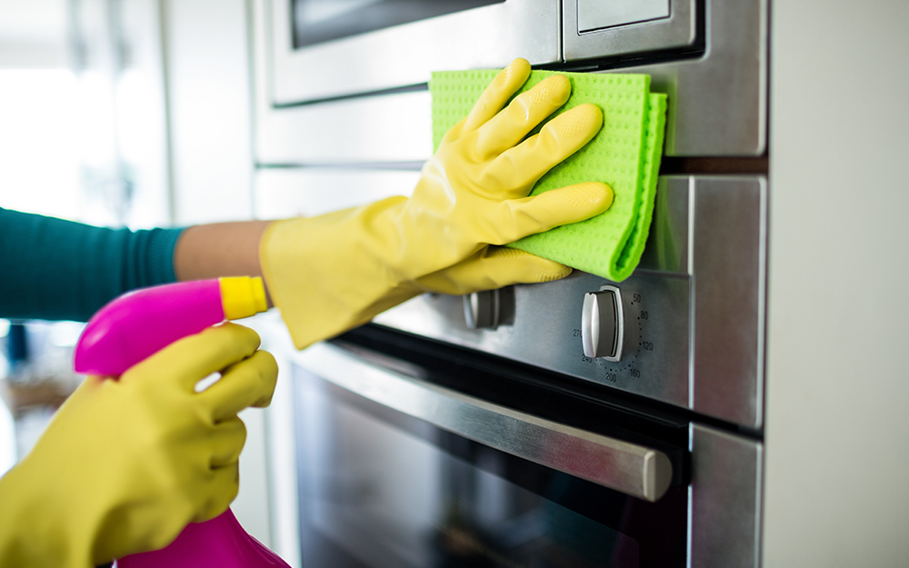 A person wearing gloves and cleaning the exterior of a wall oven with a sponge and spray bottle