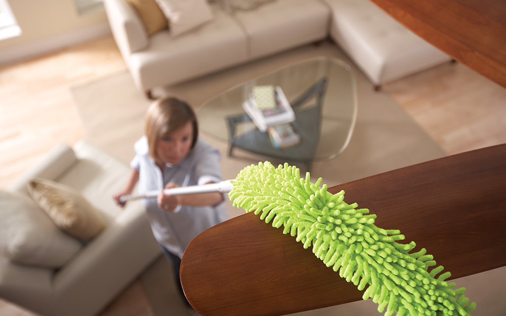 Woman using a telescoping dust mop to clean ceiling fan blades.