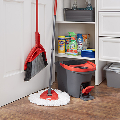 Broom, mop and other cleaning supplies in an open closet.