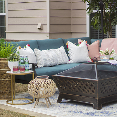 A Spring patio with an outdoor sectional and fire pit.