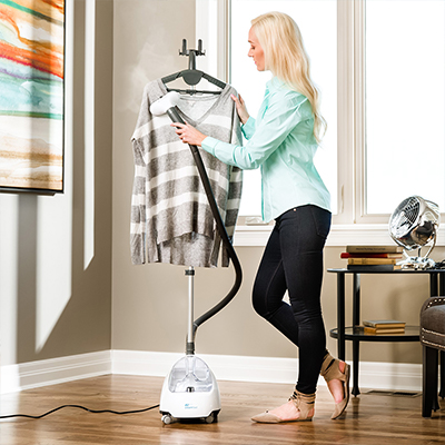 Woman is steaming a shirt in her living room.
