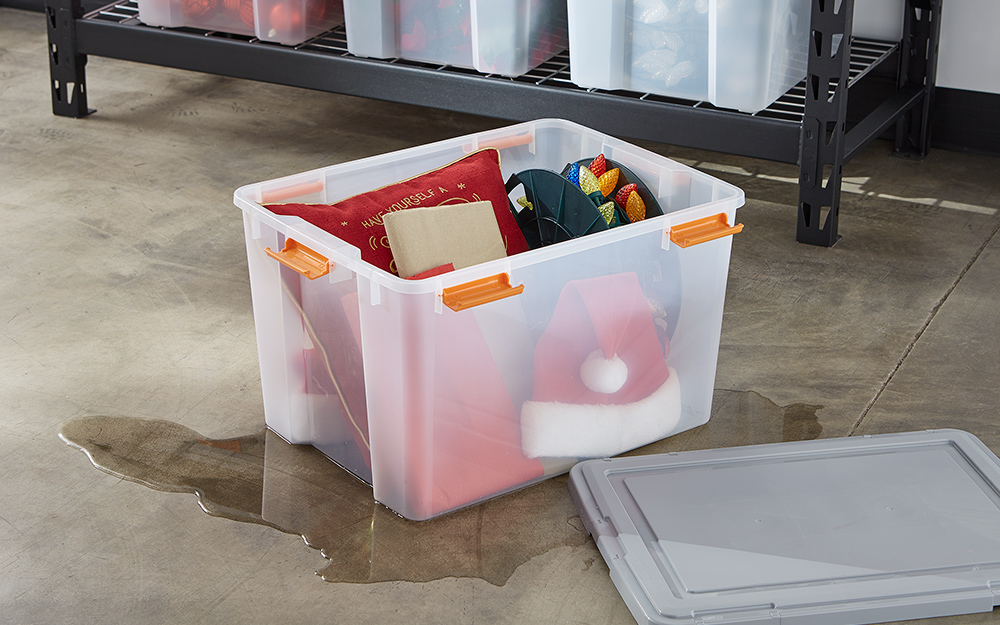 a plastic storage bin holding christmas decorations with spilled water around the bottom