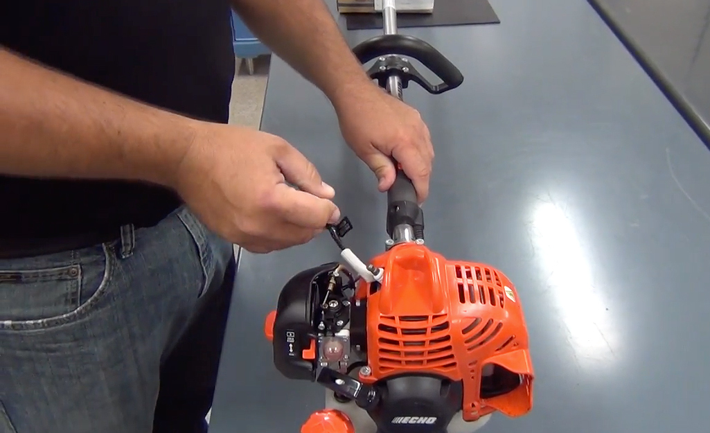 A man adjusting a part on a string trimmer.