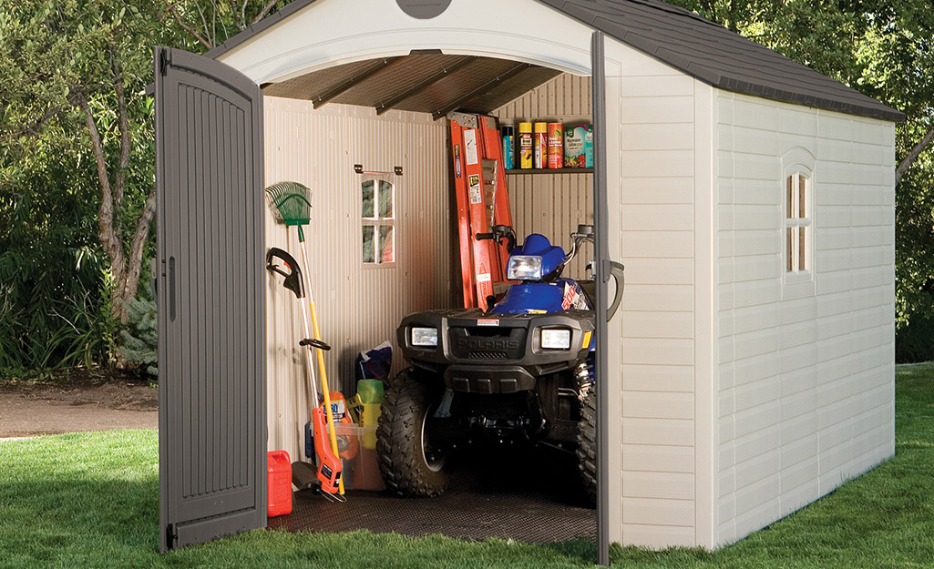 A backyard storage shed showing a string trimmer and other lawn tools.