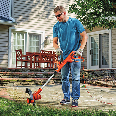 A man using a string trimmer in a backyard.