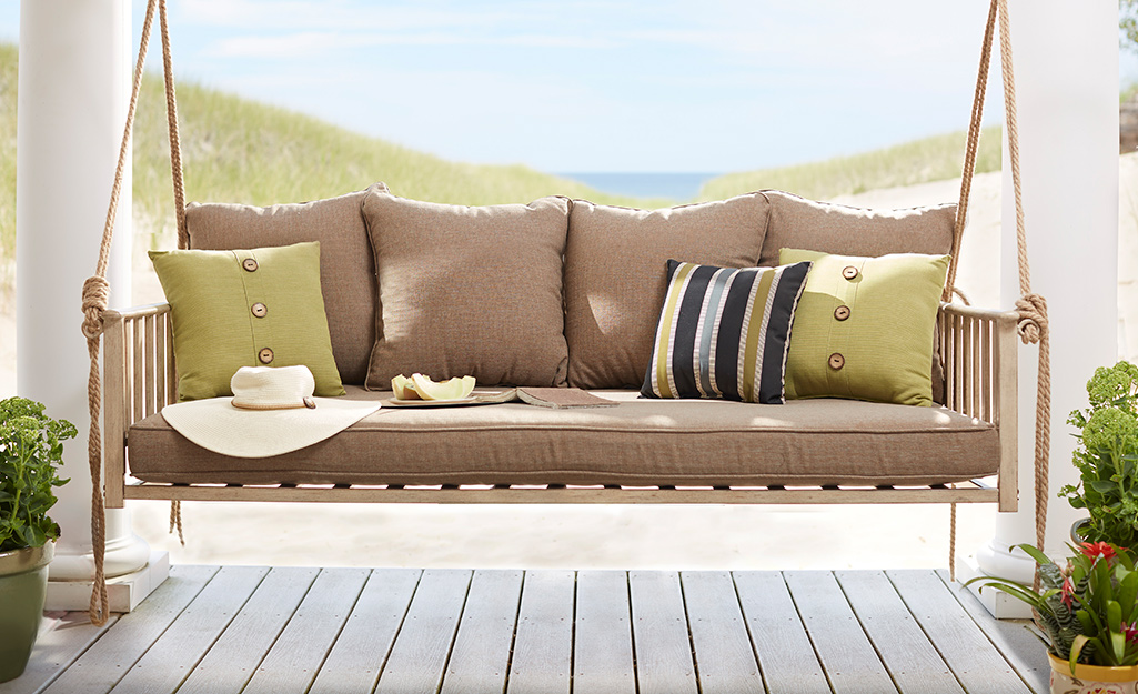 A porch swing with colorful pillows.