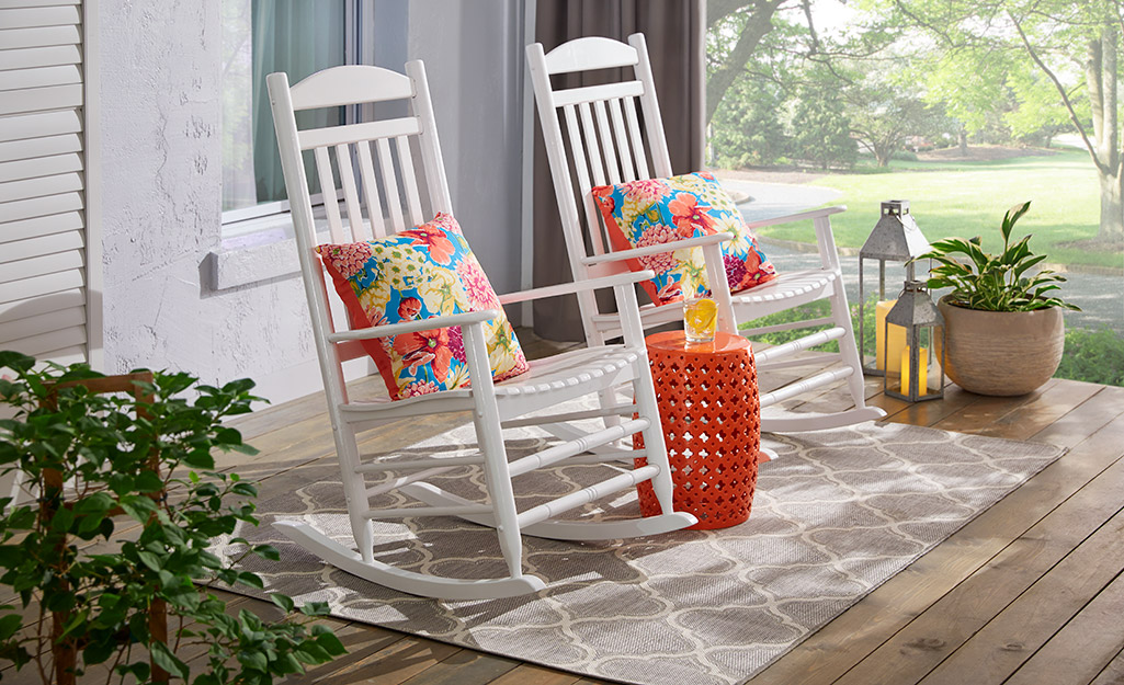 Two white rocking chairs and a garden stool sit on an outdoor rug.