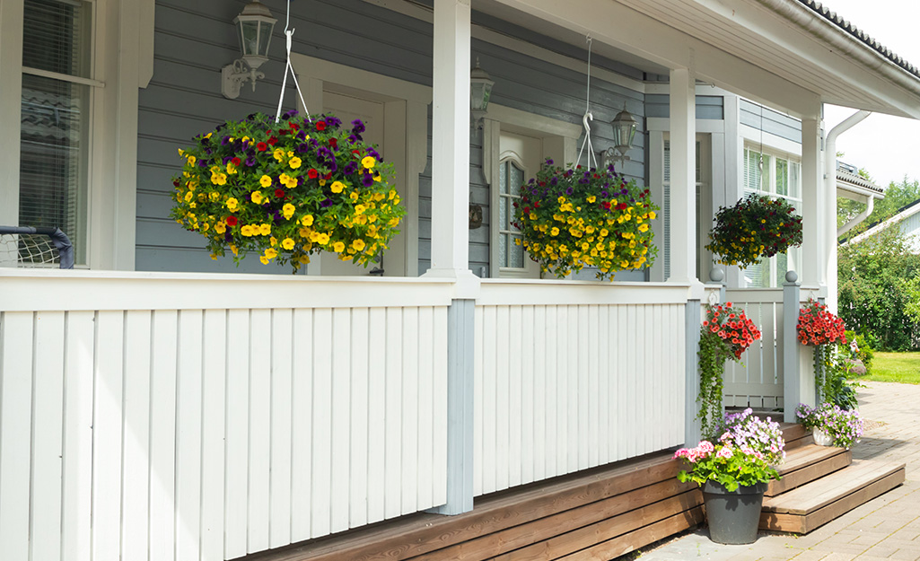 Hanging flower baskets and potted plants decorate a porch.