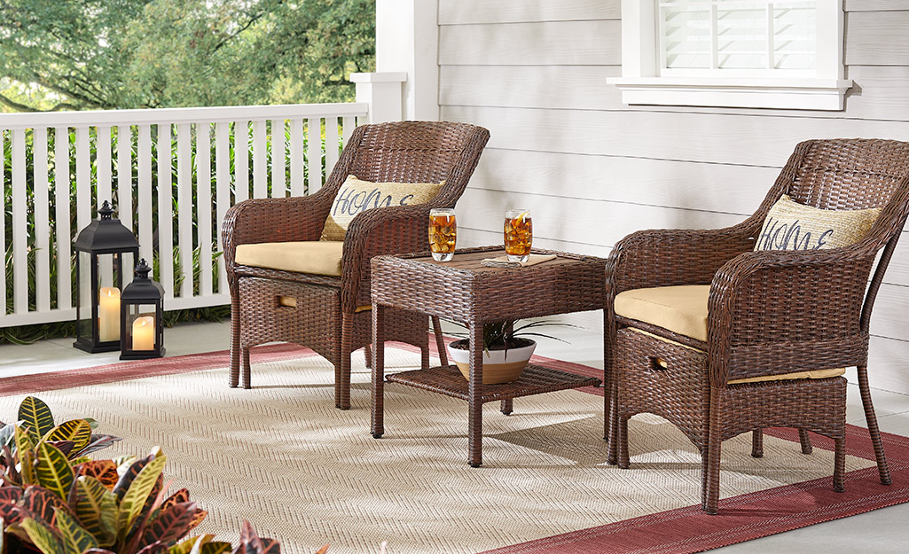 Outdoor furniture, rugs and lanterns on a porch.