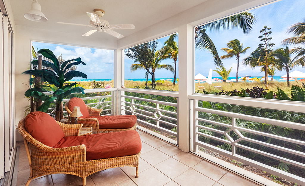 A porch with a white outdoor ceiling fan.