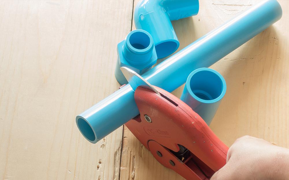 Một người dùng máy cắt ống để cắt ống nhựa PVC.
