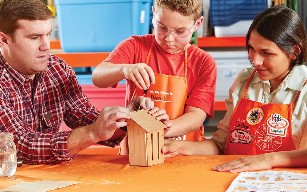Một đứa trẻ và hai người lớn xây một ngôi nhà bướm.