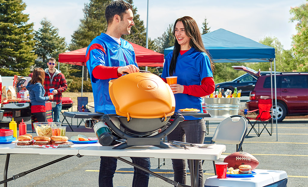 Two people use a portable grill at a tailgate.
