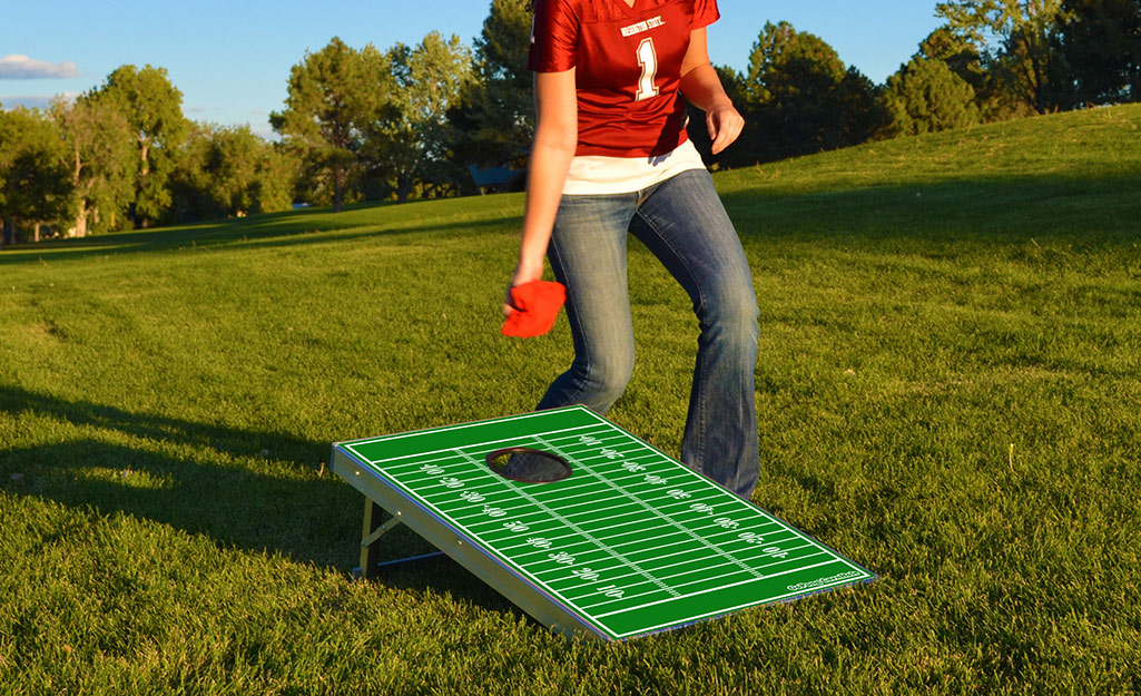 A woman plays a game of cornhole on the lawn during a tailgate.